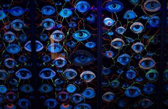 Collage con decenas de ojos en luz de neón y colores fluor contrastan con el fondo oscuro