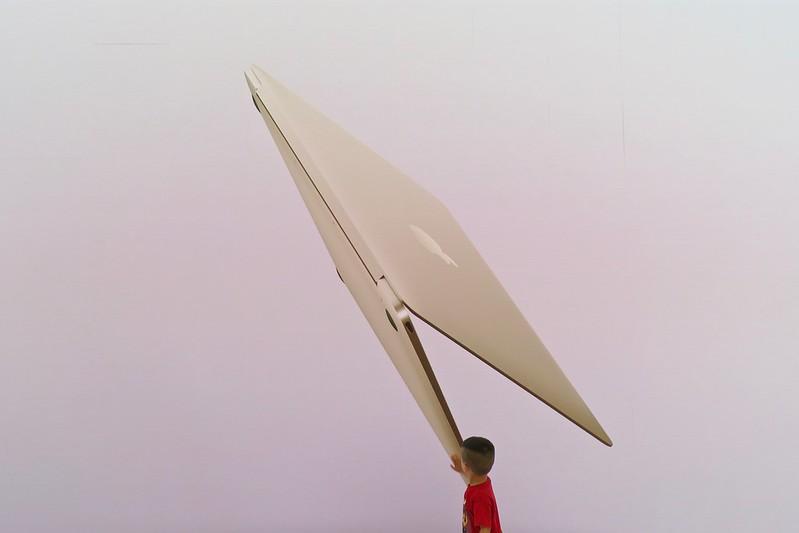 Collage fotográfico Digital- Un niño pequeño se ve de espaldas con camista anaranjada. Detrás aparacee una mac semi abierta en gran tañano.