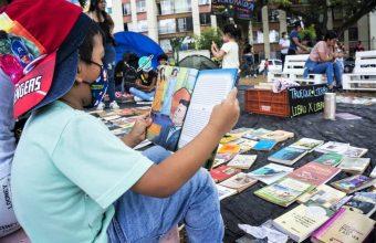 Foto con niño sentado de perfil leyendo un libro en una feria de trueque de libros en Colombia.